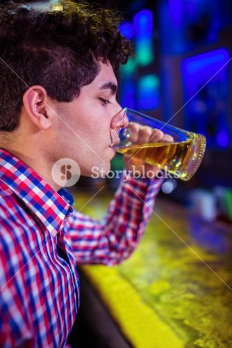 Man drinking beer at bar counter