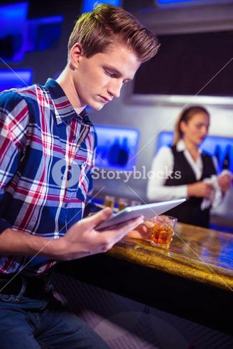 Man using digital tablet with bartender working
