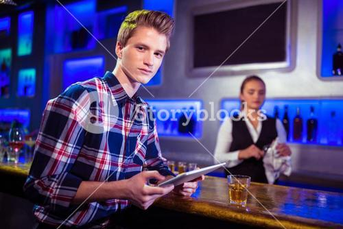 Portrait of man using digital tablet with bartender working