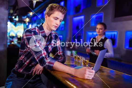 Man using laptop at bar counter with bartender working