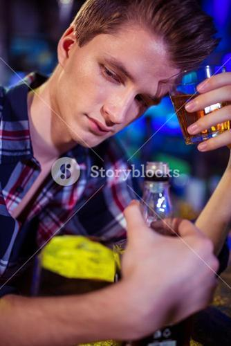 Sad man holding whiskey glass