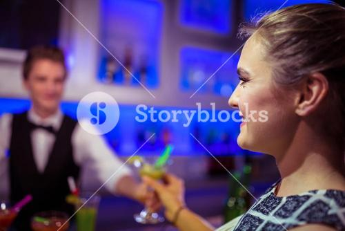 Barman serving cocktail to woman
