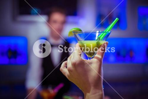 Cropped hand of customer holding cocktail glass against bartender