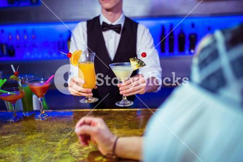 Bartender serving cocktail to woman