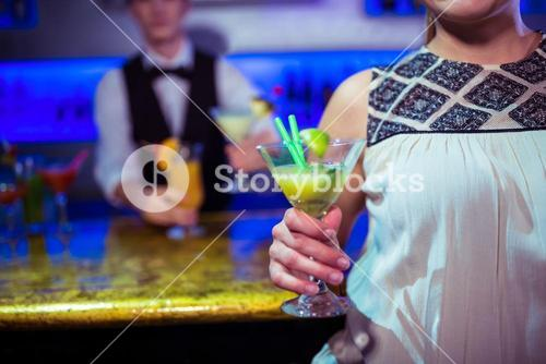 Woman with cocktail glass standing by bartender