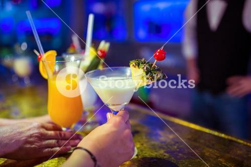 Cropped image of customers holding cocktail glasses by bartender
