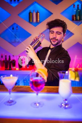Bartender with cocktail shaker at bar counter