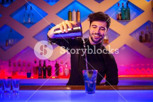 Barkeeper pouring cocktail in glass at counter