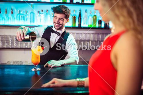 Bartender pouring cocktail in glass for customer