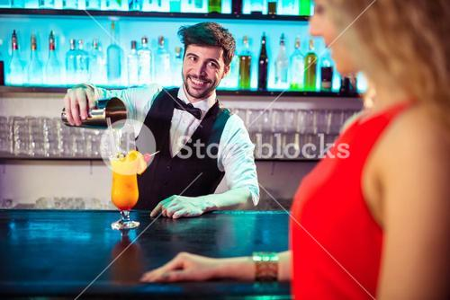 Bartender looking at woman while pouring cocktail in glass