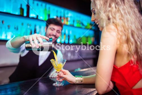 Bartender serving cocktail to young woman at counter