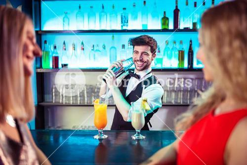 Barkeeper preparing cocktail for female customers