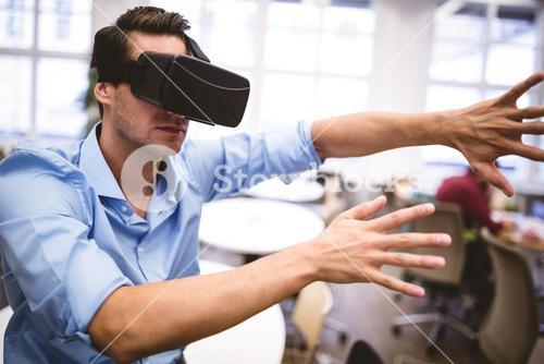 Executive gesturing while using virtual reality glasses at office