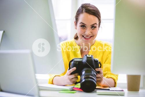 Portrait of confident professional with digital camera and computer at office