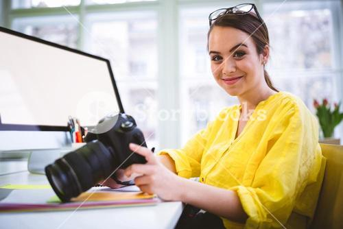Portrait of confident female professional with camera at editing office
