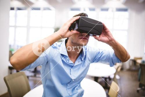 Executive holding virtual reality headset sitting at office