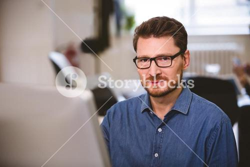 Portrait of confident executive with computer at office