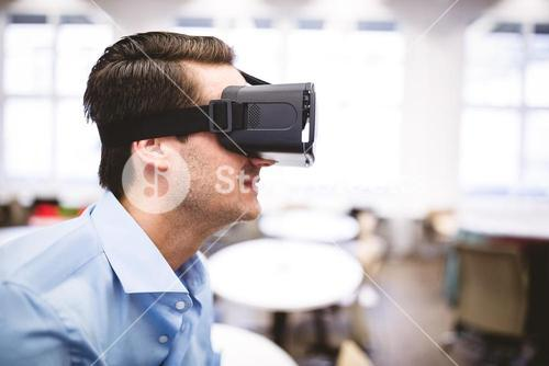 Side view of executive enjoying virtual reality headset at office