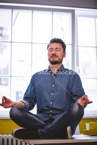 Executive meditating in lotus position at creative office