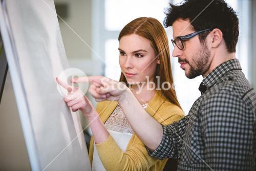 Business people pointing on whiteboard
