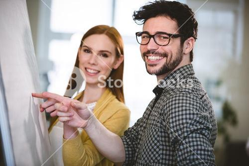 Smiling business people pointing on whiteboard