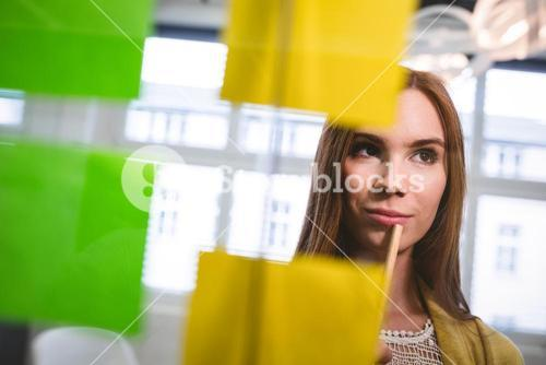 Businesswoman looking at sticky notes