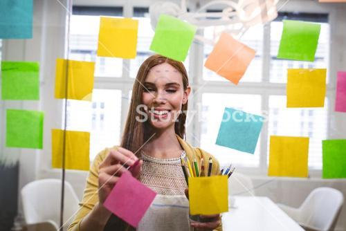 Businesswoman writing on sticky notes