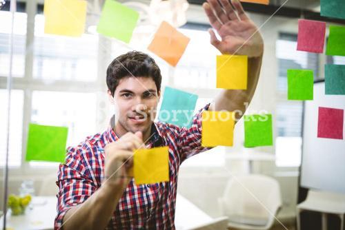 Businessman writing on multi colored sticky notes