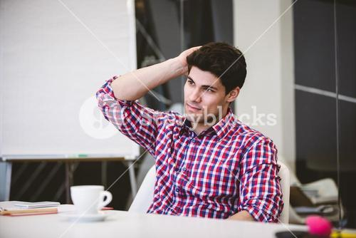 Thoughtful businessman scratching head