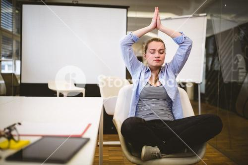 Businesswoman performing yoga in meeting room
