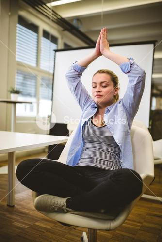 Businesswoman meditating in meeting room