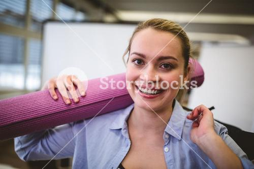 Happy businesswoman with bag and exercise mat