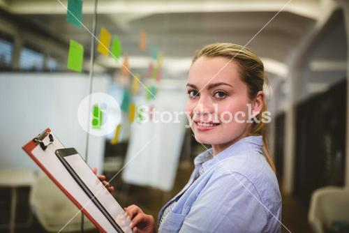 Businesswoman holding note pad and digital tablet in creative office