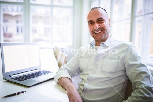 Smiling businessman sitting by laptop