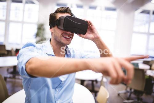 Male graphic designer gesturing while using virtual reality headset