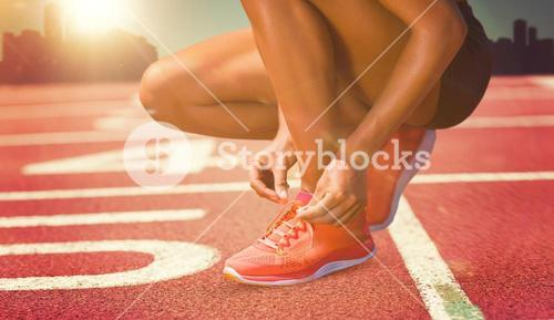 Composite image of close up of sportswoman is lacing shoes