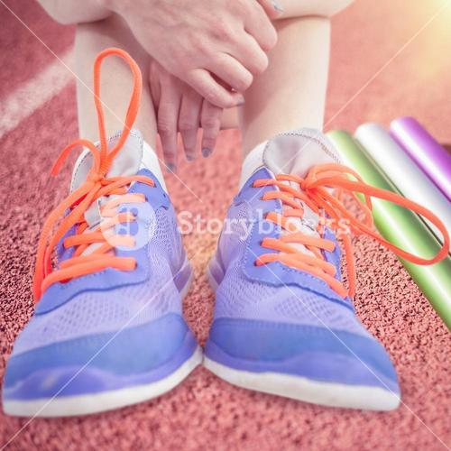 Composite image of athlete woman sitting with sports shoes
