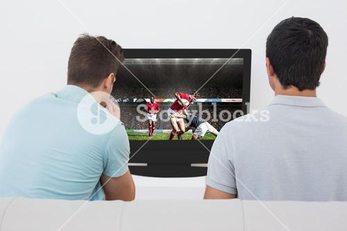 Composite image of two soccer fans watching tv