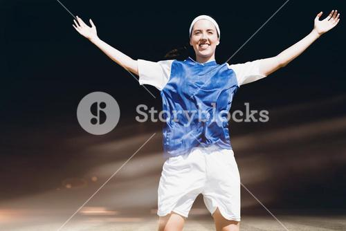 Composite image of front view of happy sportswoman raising her arms