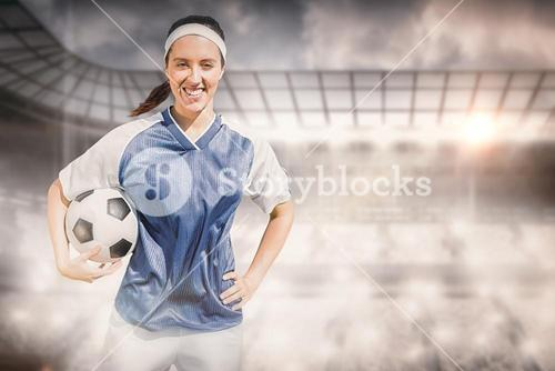 Composite image of portrait of happy woman football player holding a football