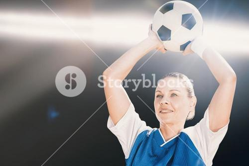 Composite image of woman soccer player holding a ball