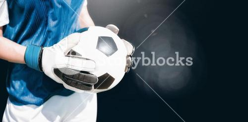 Composite image of close up of a football held by sportswoman