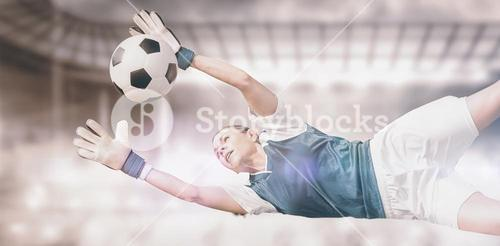 Composite image of woman goalkeeper stopping a goal