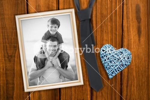 Composite image of father giving son piggyback ride