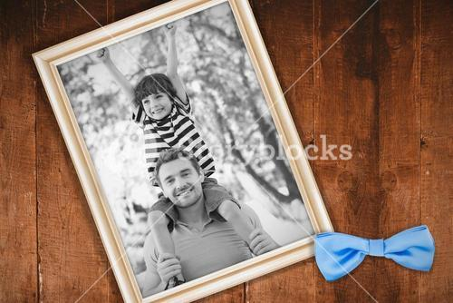 Composite image of father carrying a happy son on shoulders at park