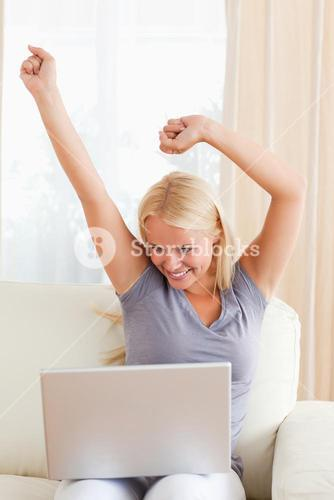 Portrait of an excited woman using a laptop