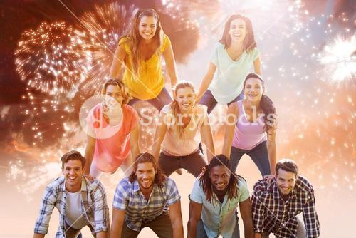 Composite image of happy friends making human pyramid