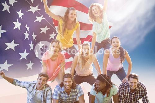 Composite image of happy friends in the park making human pyramid