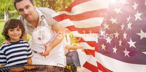Composite image of father and son at barbecue grill with family having lunch in park