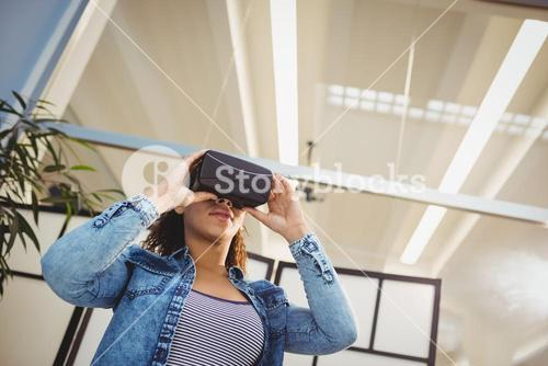 Low angle view of businesswoman enjoying virtual reality headset at office